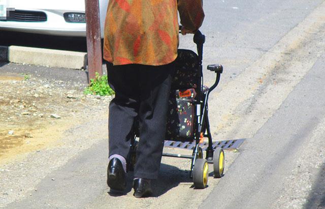 シルバーカーを押して歩く高齢者